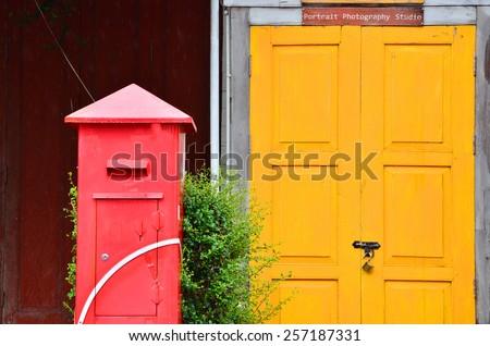 Red post box in front of the yellow wooden door - stock photo