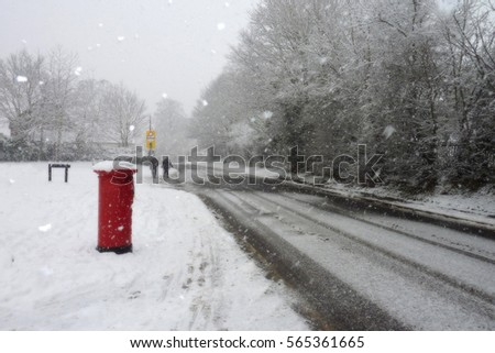 Red post box in snowbound road with figures in distance
