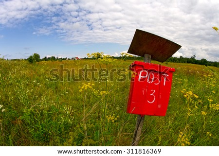 Red postbox in a rural setting - stock photo