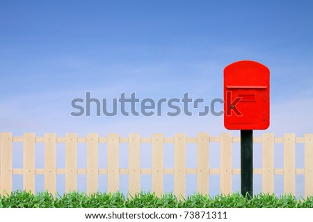 red postbox with white fence and clear blue sky - stock photo