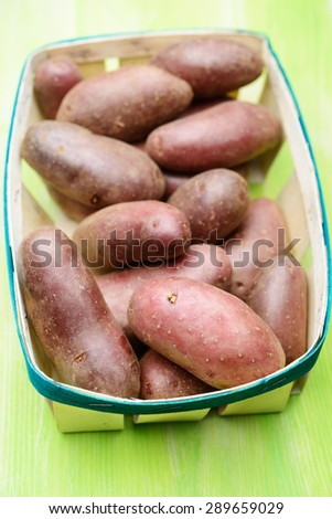 Red potato in a basket. Selective focus on the front edge of basket - stock photo
