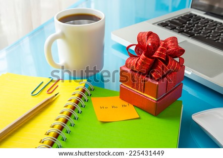 Red present box and paper note with Merry christmas message: Ho Ho Ho! place on office table with laptop, colorful diary and a cup of coffee, concept to christmas gift and holiday season - stock photo
