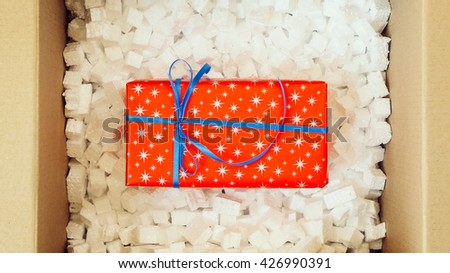Red present box in big shipping box. Opening a parcel contains a gift. Unpacking box with another box. Surprise. People, delivery, shipping service, opening cardboard box or parcel at home. - stock photo