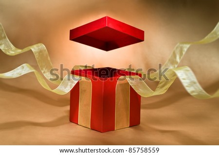 Red Present Box with open cover and yellow flying ribbon - stock photo