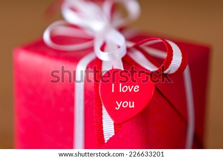 Red present with white bow and heart on brown background, text, I love you - stock photo