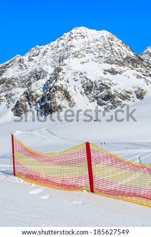 Red protection net on ski slope in the mountains of Pitztal winter resort, Austrian Alps  - stock photo