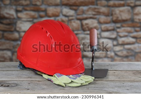 Red protective helmet, gloves and bricklayer trowel lie on rough wooden table on blurred stone wall background. Masonry and building profession concept - stock photo