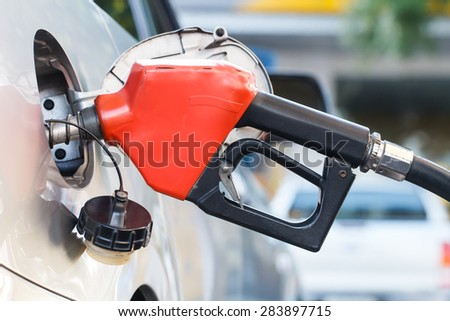 Red pumping fuel oil in car at gas station - stock photo