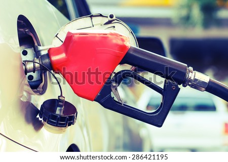 Red pumping fuel oil in car at gas station-retro - stock photo