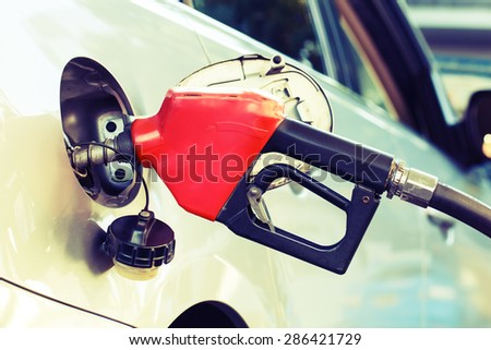 Red pumping fuel oil in car at gas station, retro - stock photo