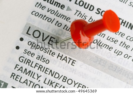 Red push pin near the word LOVE on a dictionary page - stock photo