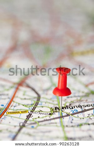 red push pin stuck in a map close up