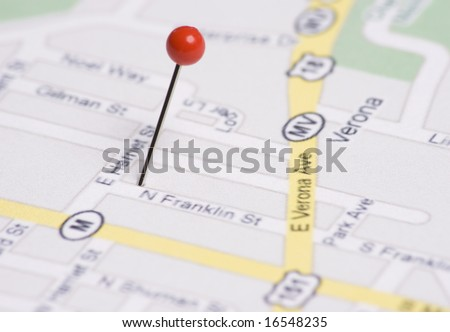 Red push pin stuck in map - stock photo
