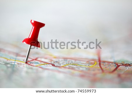 Red pushpin showing the location of a destination point on a map - stock photo