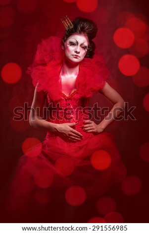 Red Queen. Woman with creative make-up in fluffy red dress posing over glowing lights background