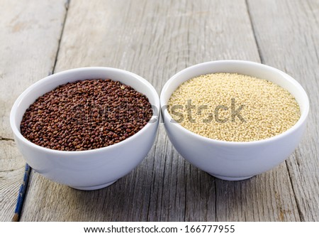 Red quinoa and amaranth in white bowls on the vintage wooden table - stock photo