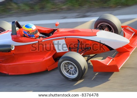 Red racing formula car in motion, all brands removed