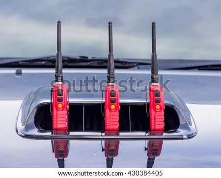 Red radio transmitter on black car  - stock photo