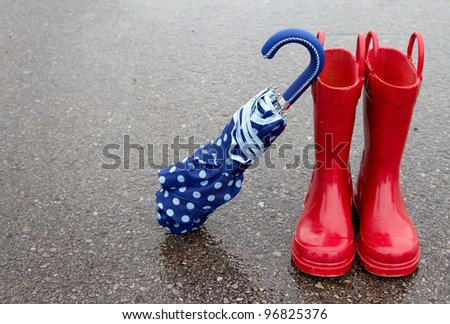 Red rain boots and polka dot umbrella on wet pavement - stock photo