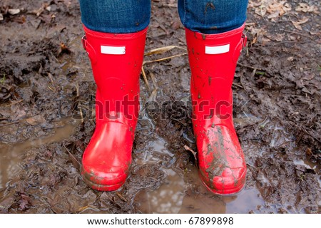 Red rain boots on the legs of a girl after she played in the mud and got them dirty and muddy.