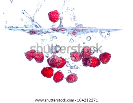 Red Raspberries Falls under Water with a Splash, isolated - stock photo