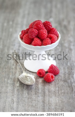 Red raspberries on white stand on grey wooden background with silver spoon - stock photo