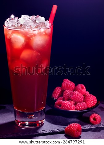 Red raspberry drink  with ice cube and plate of berry on black background. Cocktail card 18 - stock photo