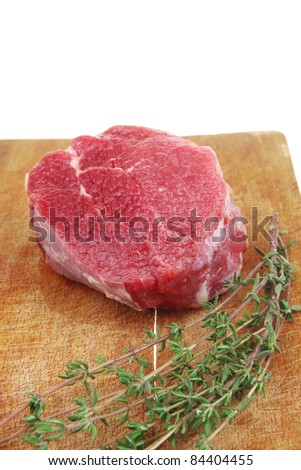 red raw fillet chops : fresh beef meat with thyme on wooden plate . isolated over white background - stock photo