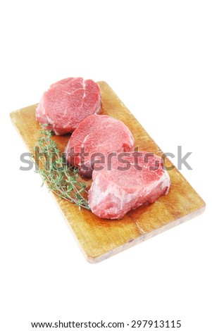 red raw fillet chops : three fresh beef meat chops with thyme twig on wooden plate . isolated over white background - stock photo