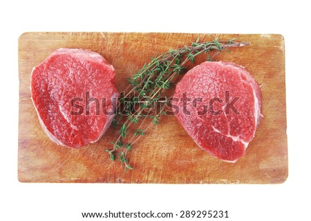 red raw fillet chops : two fresh beef meat chops with small thyme twig on wooden plate . isolated over white background - stock photo