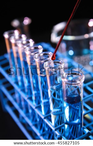 Red reagent dropped into test tube containing blue chemicals