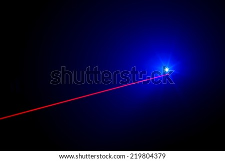 Red real laser beam with LED light on black background - stock photo