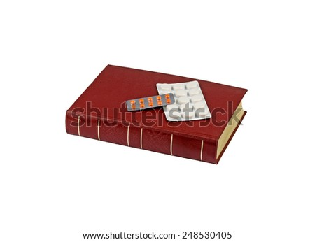 Red recipe book and two blister pack medicine pills are isolated on white background - stock photo