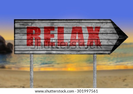 Red Relax wooden sign with a beach on background