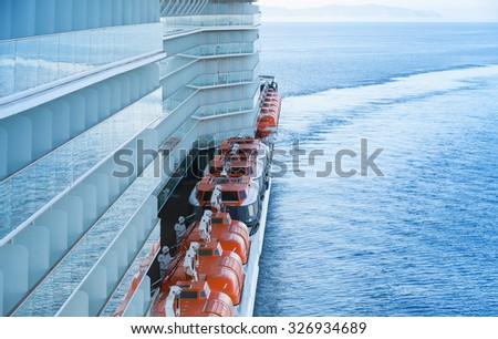 Red rescue boats in a row mounted on the deck of big passenger ferry - stock photo