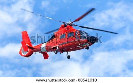Red rescue helicopter moving in blue sky with blur propeller - stock photo