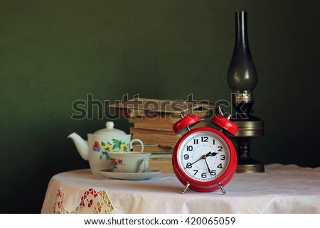 Red retro alarm clock on table with white tablecloth with lace. In the background a stack of books, kerosene lamp and an old teapot and teacup for tea. Retro still life with alarm clock. - stock photo