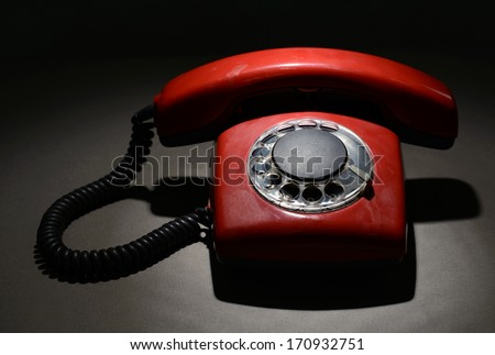 Red retro telephone on dark color background