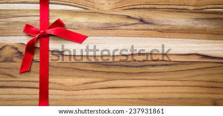 red ribbon and bow on a beautiful and exotic wooden background - stock photo