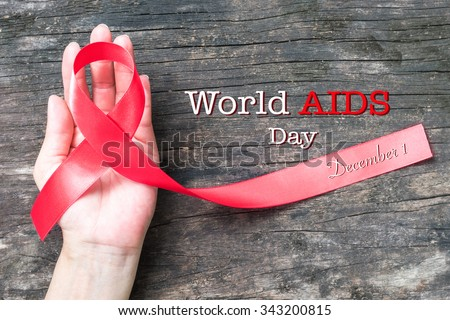 Red ribbon awareness on human hand with aged wood background with text message World aids day December 1: Symbolic concept for raising awareness/ concerns/ help and campaign on people with HIV concept - stock photo