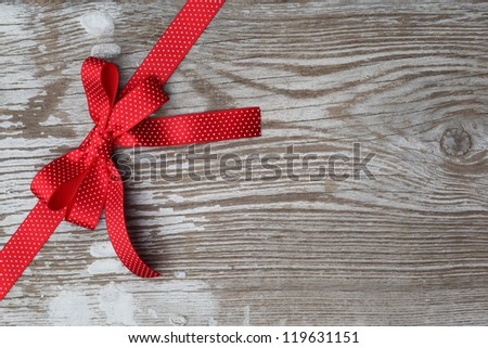 Red ribbon bow on wooden board with copy space - stock photo