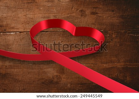 Red ribbon heart against overhead of wooden planks - stock photo