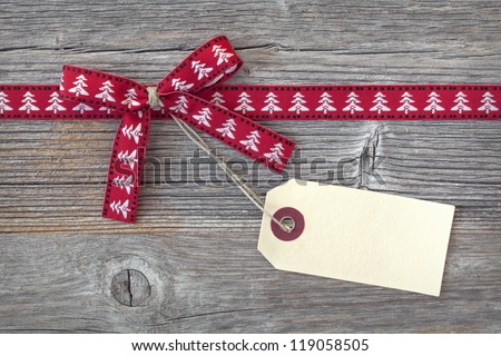 Red ribbon with a tag on wooden background - stock photo