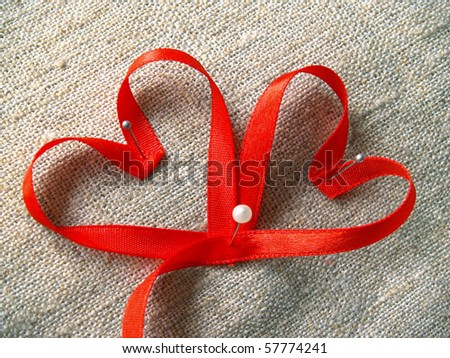 red ribbons heart on the rough canvas - stock photo