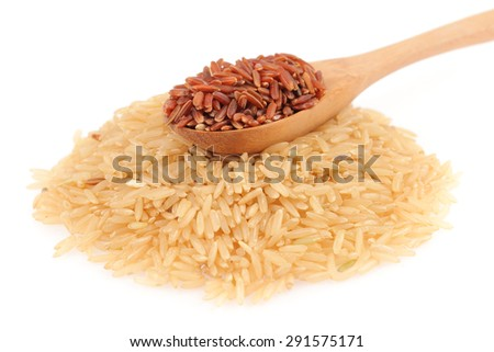 Red rice in a wooden spoon and pile of brown rice isolated on white background