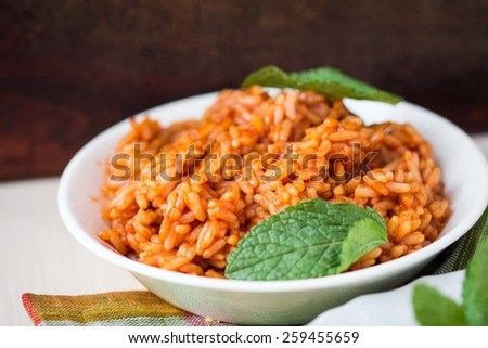 Red rice, risotto with tomatoes, easy vegetarian dish - stock photo