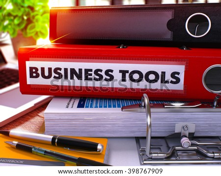 Red Ring Binder with Inscription Business Tools on Background of Working Table with Office Supplies and Laptop. Business Tools Business Concept on Blurred Background. 3D Render. - stock photo
