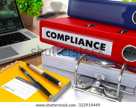Red Ring Binder with Inscription Compliance on Background of Working Table with Office Supplies, Laptop, Reports. Toned Illustration. Business Concept on Blurred Background. - stock photo