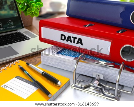 Red Ring Binder with Inscription Data on Background of Working Table with Office Supplies, Laptop, Reports. Toned Illustration. Business Concept on Blurred Background. - stock photo