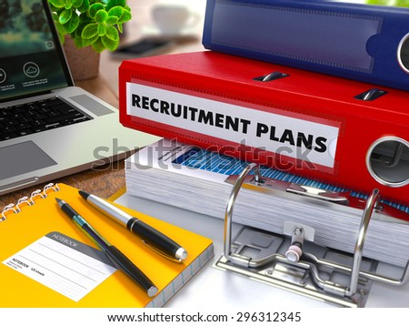 Red Ring Binder with Inscription Recruitment Plans on Background of Working Table with Office Supplies, Laptop, Reports. Toned Illustration. Business Concept on Blurred Background. - stock photo